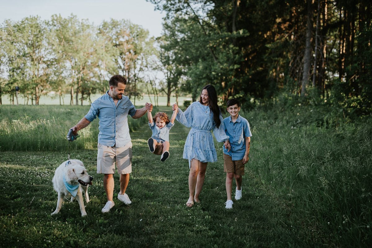 A family with two sons and a dog walk through a park smiling.