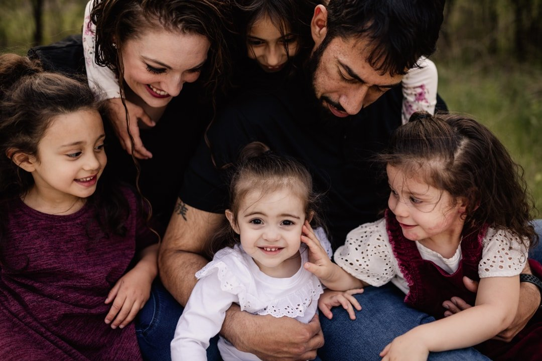 A family of six gazes down at the youngest child and smiles.