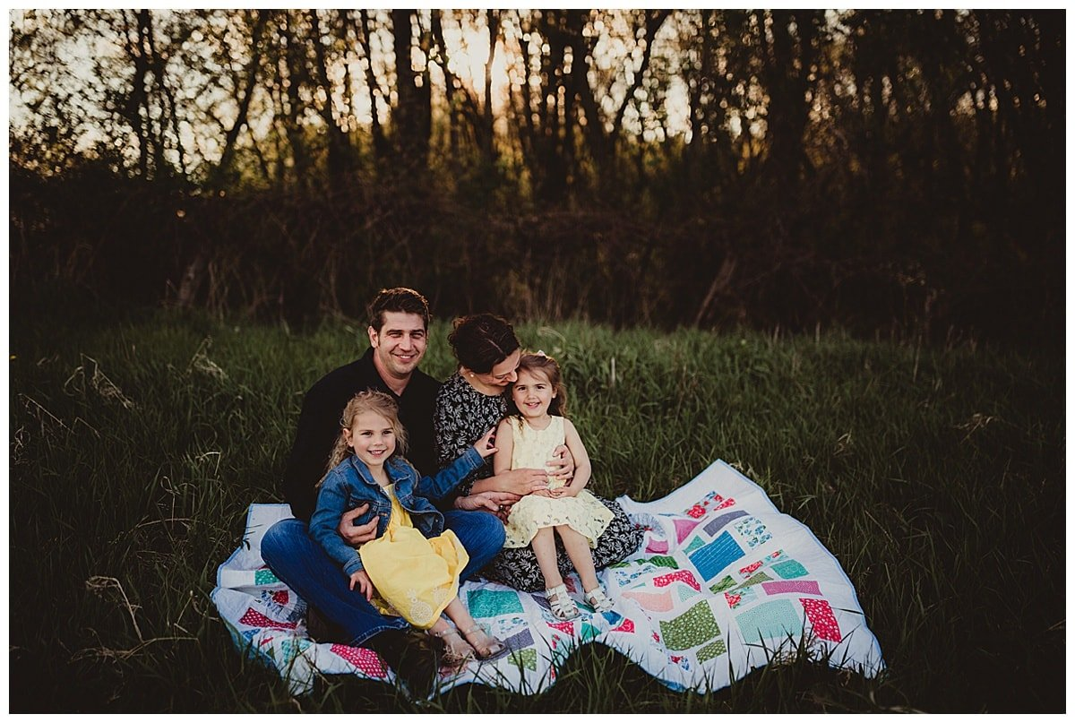 A family of four sits on a quilt in a park.