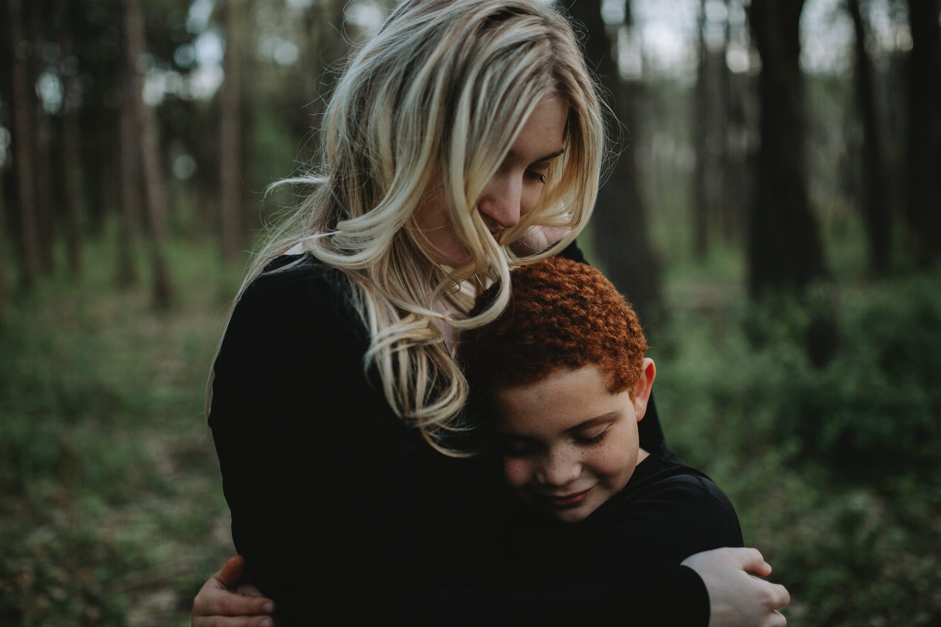 A mother and her son embrace in the forest at Anderson Farm County Park in Oregon, WI.