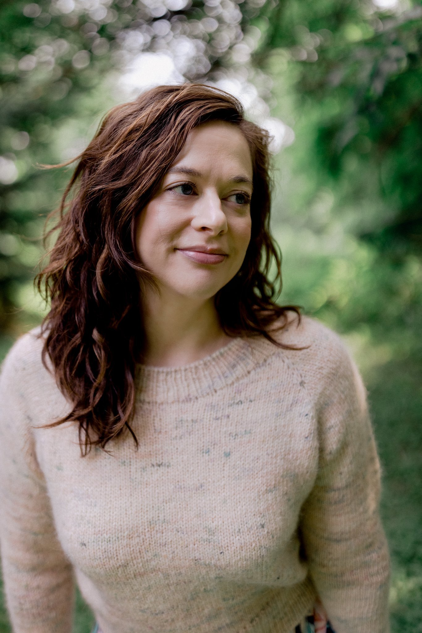 A woman in her mid-thirties stands amongst green trees wearing a handknit soft pink sweater. She softly smiles and gazes off to the side.
