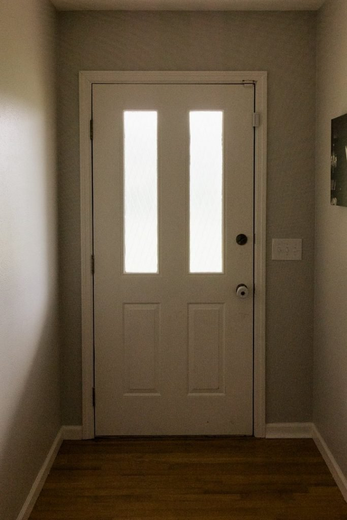 A rarely used front door at the end of a dark hallway. A rarely seen wedding photo is on the hallway wall.