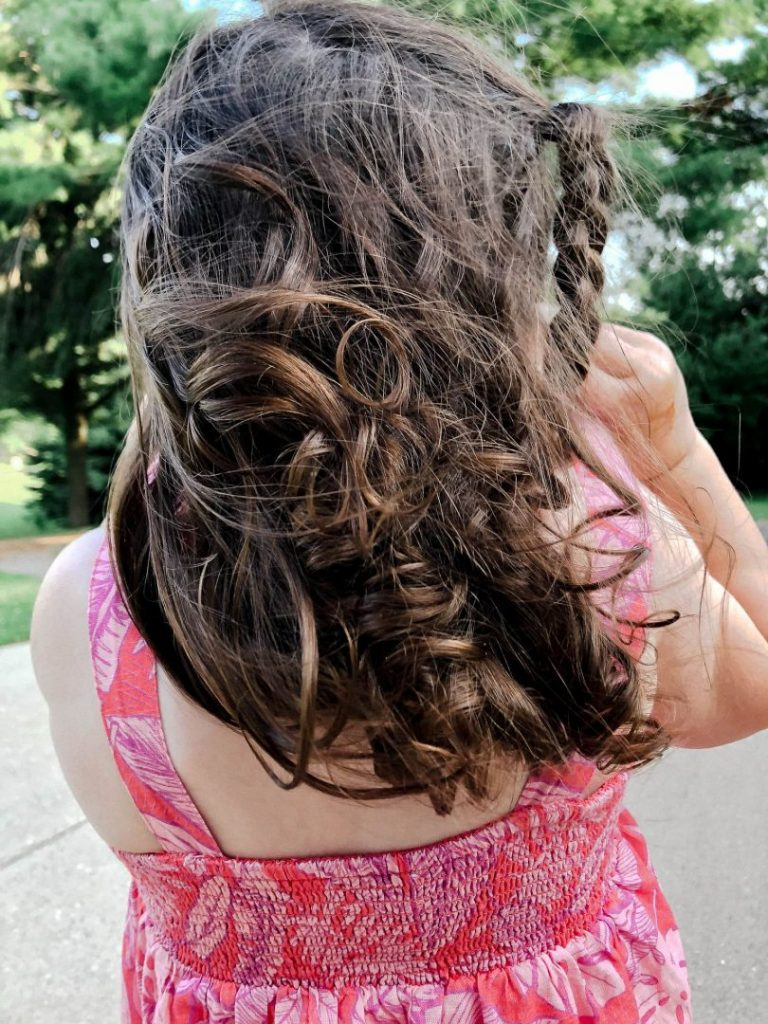 An iPhone photo of a toddler girl's curly brown hair blowing in the wind.